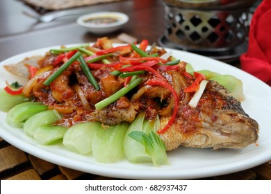 Large-sized fried carp fish served with vegetables during Chinese new year celebrations in Indonesia.