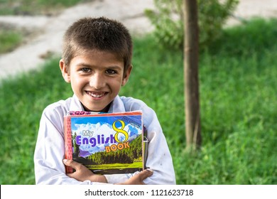 Larkana,sindh/Pakistan,May 17 2018: a poor villager boy is holding english books smiling and going to school.