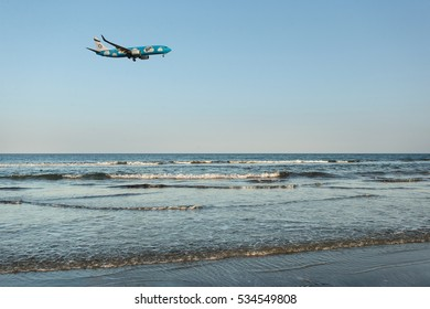 LARNACA, CYPRUS - February 23, 2016: Low-cost brand of Israeli airline El Al - Up landing at Larnaca International Airport straight from sea. Beautiful evening sunset landscape.