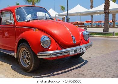 LARNACA, CYPRUS - JUL 15: Vintage red Volkswagen VW Beetle car (Volkswagen Type 1, Volkswagen Bug) parked near the Finikoudes Beach (Larnaca Promenade) on July 15, 2013 in Larnaca, Cyprus.