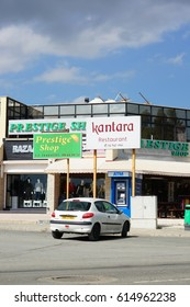 LARNAKA, CYPRUS - MARCH 13, 2017: Parked car in front of a Prestige Shop selling clothes and souvenirs on a sunny day