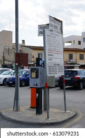 LARNAKA, CYPRUS - MARCH 14, 2017: Ticket vending machine with information sign on a parking lot with many cars
