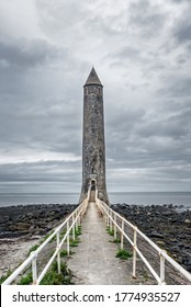 Larne, UK -  July 4, 2020: Chaine Memorial Irish round tower replica and lighthouse on the north antrim coast in Larne