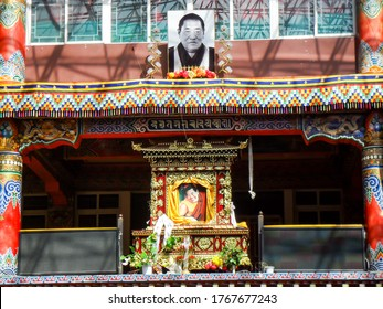 Larung Gar, China - October 10 2019 : Main prayer hall with picture of leader lama or Tibetan Bla-ma on the main building in Larung Gar Buddhist Institute.