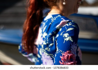 Larvik, Norway - April 22nd 2019: Woman, with red hair, in blue blouse, with flower pattern