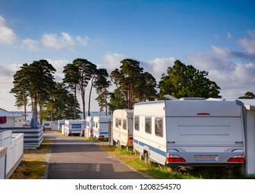 LARVIK, NORWAY - JULY 20, 2018: Camper trailers and cabins at seaside holiday park in a morning light