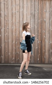 Larvik, Norway - July 28th 2019: girl model, wearing a short black dress and a denim jacket, standing in front of a wooden wall.