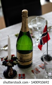 Larvik, Norway - May 17th 2019: Table set for  Norways national day celebration. Decorated with Norwegian flags. Green champagne bottle