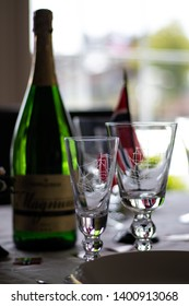 Larvik, Norway - May 17th 2019: Table set for Norways national day celebration. Decorated with Norwegian flags. Green champagne bottle. Drinking glasses in focus.