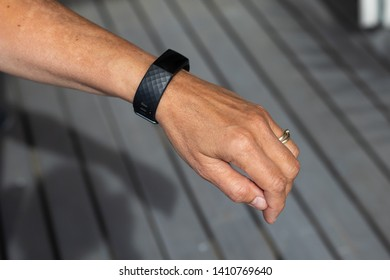 Larvik, Norway - May 26th 2019: Woman's hand with a Fitbit charge 3 around her wrist