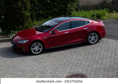 Larvik, Norway - May 31st 2019: Red Tesla car parked in driveway.