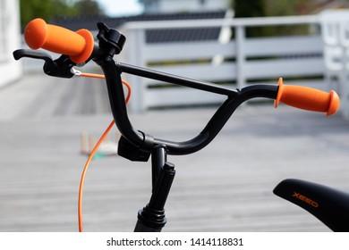 Larvik, Norway - May 31st 2019: Black kids bike with orange details.