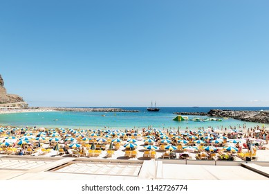 Las Americas, Canarias islands/ Spain-July 22, 2018: View of beach fool of tourists and umbrellas for sun on Canarias, view of bay with mountains. Blue Atlantic ocean and beach on Gran Canaria.