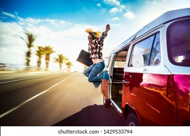 Las Americas, Tenerife / Spain - 10 15 20Happy middle age woman jumping outside a red vintage van while traveling fast on the road for the joy to start the vacation or adventure - wanderlust lifestyle