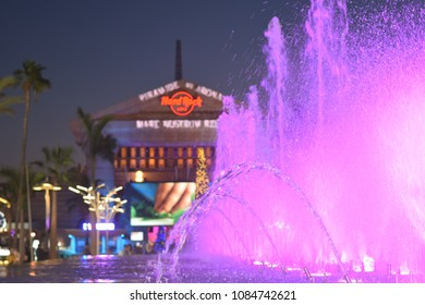 Las Americas, Tenerife/ Spain - 12.22.2017: beautiful violet dancing fountain on a background of Hard Rock Cafe.