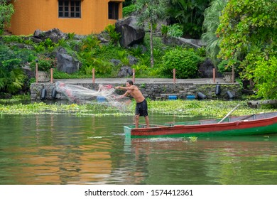 Las Isletas, Granada, Nicaragua - Oct 31, 2019: Local native Indian fisherman in a wooden boat throwing fish net into the river water. Selective focus.