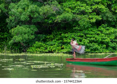 Las Isletas, Granada, Nicaragua - Oct 31, 2019: Local native Indian fisherman in a wooden boat throwing fish net into the river water. Lush green tropical forest in the background. Selective focus.