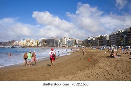 LAS PALMAS DE GRAN CANARIA, SPAIN - DECEMBER 31: Local and tourists enjoy sun on New Year eve on Las Canteras town beach, December 31, 2017  in Las Palmas de Gran Canaria, Spain