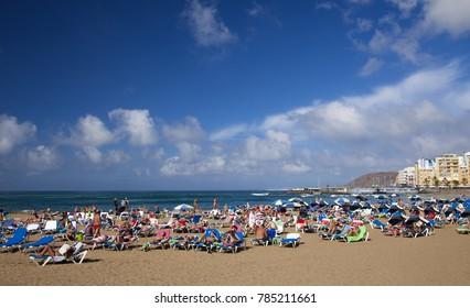 LAS PALMAS DE GRAN CANARIA, SPAIN - DECEMBER 31: Locals and tourists enjoy sun on New Year eve on Las Canteras town beach, December 31, 2017  in Las Palmas de Gran Canaria, Spain
