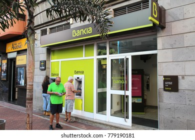 LAS PALMAS, SPAIN - NOVEMBER 30, 2015: People visit Bankia bank branch in Las Palmas, Spain. Bankia is a Spanish bank conglomerate, the fourth largest bank of Spain with 12 million customers (2012).