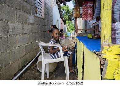 LAS TERRENAS, DOMINICAN REPUBLIC - SEPTEMBER 26, 2016: unidentified little girl helps mother to sell some food and staff. In the D.R. more than 40% of the population lives below the poverty line.