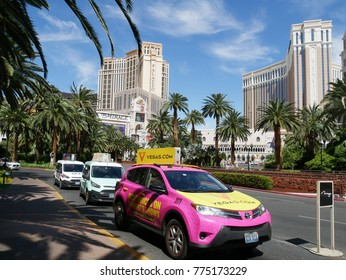 LAS VEGAS, NEVADA—APRIL 2017: Bright colored taxicabs wait in line for passengers across from big hotels like the Palazzo and Venetian at the Las Vegas Strip in Nevada.