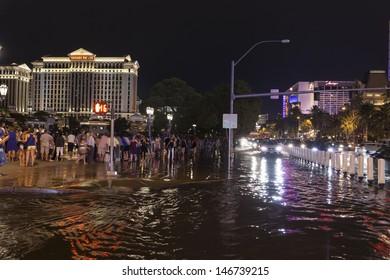 LAS VEGAS - JULY 19, - Vegas Strip on July 19, 2013 in Las Vegas. Tourists gather for the fountains at Bellagio despite major flooding feet away on the strip.