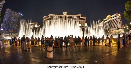 LAS VEGAS - JUNE 15: people watch the famous fountain show at Las Vegas Bellagio Hotel Casino at night on June 15, 2012 in Las Vegas, Nevada.