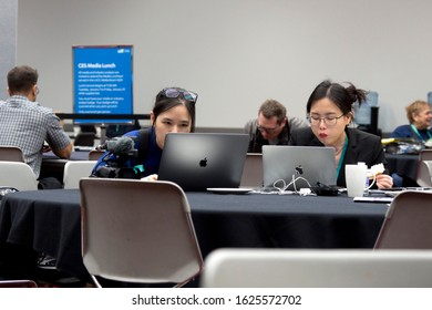 LAS VEGAS, NEVADA - January 9, 2020: Two young asian girls with laptops having a lunch break in the cafeteria at the annual Consumer Electronics Show