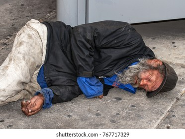 """LAS VEGAS, NEVADA - MAY 5, 2013: A homeless man """"rests"""" near a bus stop on the Las Vegas Strip."""