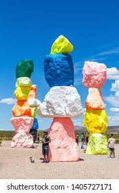 LAS VEGAS, NEVADA, USA - 12 MAY, 2019: Seven Magic Mountains art installation near Las Vegas city. Pillars made of neon colored boulders stand against barren desert background and blue sky.