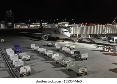 LAS VEGAS, NEVADA, USA - FEBRUARY 2019: Alaska Airlines Airbus jet at night at McCarran International Airport in Las Vegas, with luggage trucks in the foreground.
