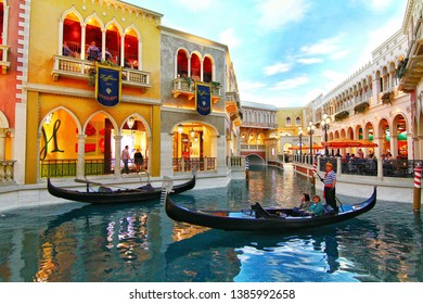 Las Vegas, Nevada, USA-25 February 2015:A gondolier on famous Italian gondola with tourists on a romantic ride on the canals of the Venetian Luxury Hotel and Casino and mall