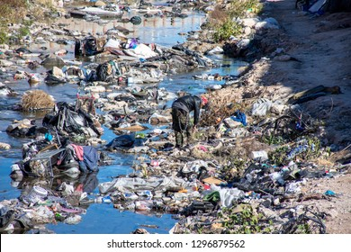 Las Vegas, Nevada/USA - January 5, 2019: Person searches through trash in waterway filled with trash near Las Vegas Strip - Homeless Pollution Environment America