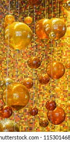 Las Vegas, Nevada/USA: May 11, 2018: Orange and Yellow Glass balls hung with wire from the ceiling at The Aria Resort and Casino Lobby