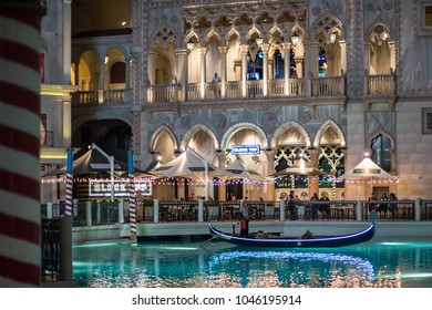 Las Vegas, NV / USA - March 8, 2017: At night, lights dance off the water from a gondola along the canal at the beautiful Venetian Hotel and Casino, a famous theme hotel on the Las Vegas Strip.