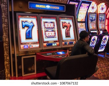 LAS VEGAS, NV/U.S.A. - FEBRUARY 18, 2018: A photo of an unidentified man sitting in front of a giant slot machine in a downtown casino.