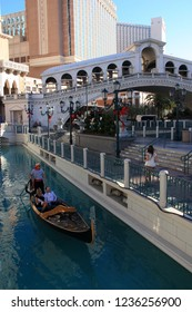 Las Vegas, NV/USA - January 6th 2012: Gondolier steering his gondola on a canal in front of the Rialto bridge replica of the Venetian Resort Hotel Casino