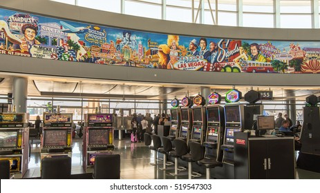 LAS VEGAS, NV/USA - NOVEMBER 7, 2016: Slot machines at McCarran Airport below a mural with The Rat Pack, Dean Martin, Sammy Davis Jr. Frank Sinatra, and the Stardust and Caesar's Palace casinos.