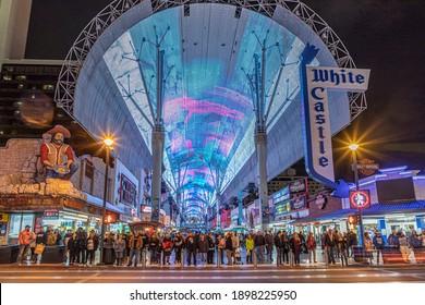 Las Vegas, USA - March 9, 2019:  people crossing the road at illuminated Casinos at Fremont street in Las Vegas by night. Fremont street was the first place for Casinos in Las Vegas.