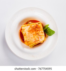 "Lasagna ""Bolognese"" on a white plate on a light background (close top view)"