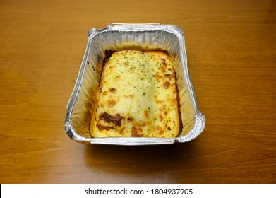 Lasagna or Lasagne is oven-baked pasta and is a traditional Italian food. It is filled with minced beef. Served on alumunium foil cup and isolated on the wooden table.