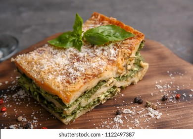 Lasagna with spinach on wooden board, close up
