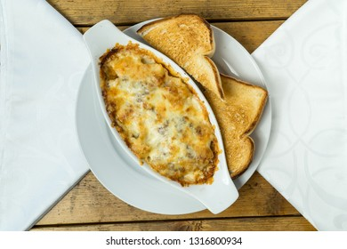 Lasagna with toast bread on wooden table