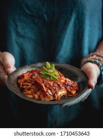 lasagnes à la sauce tomate et viande aux mains des femmes