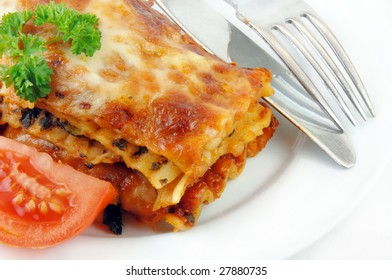 Lasagna and tomatoes with utensils on a white plate.