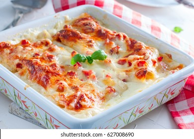 Lasagne with ham and cheese in a baking dish, horizontal