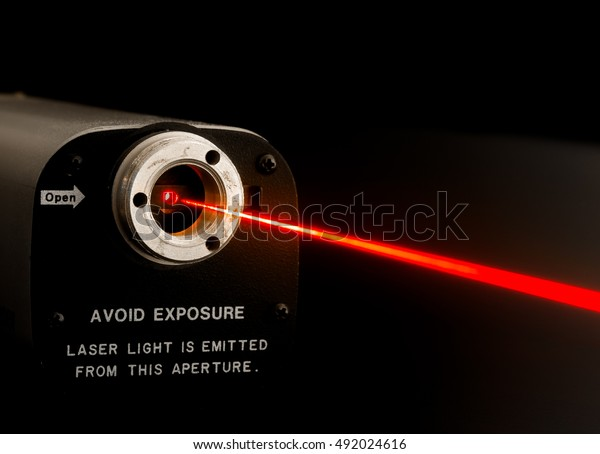 Laser beam from lab laser. Warning notice on front. Aperture is not noisy, it looks this way due to diffraction of coherent light at aperture boundary. Beam made visible by mist sprayed into air.