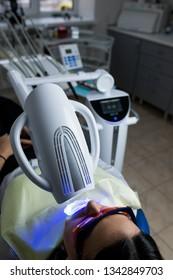 Laser bleaching teeth at dantist room. Teeth whitening for woman. Bleaching of the teeth at dentist clinic