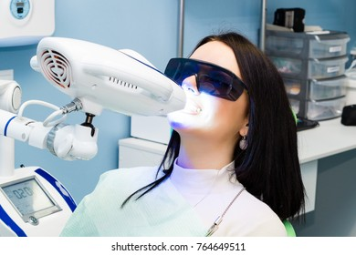 Laser bleaching teeth at dantist room. Teeth whitening for woman. Bleaching of the teeth at dentist clinic.